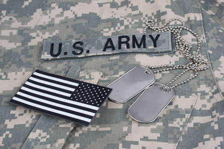 US flag patch with dog tags on camouflage Army Combat Uniform background