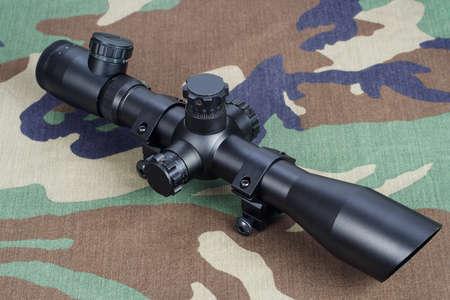 sniper optic scope on camouflaged uniform background