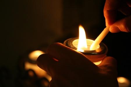 votive candle: hands lighting a votive candle