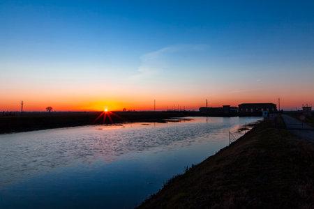 Sunset at Botti Barbarighe, Cavarzere, Venice, Italy, Veneto. Visible Drainer of Santa Giustina. Polesana remediation. Confluence of rivers. Famous hydraulic work.