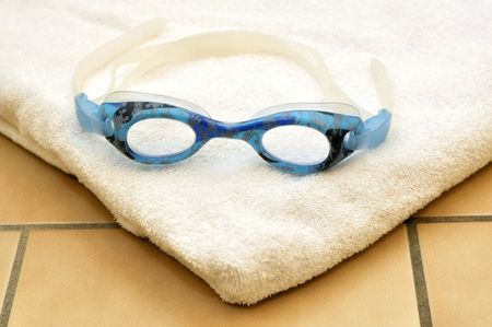 Swimming goggles on white towel