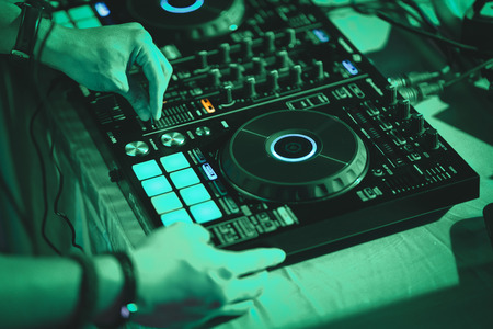 dj hands on stage mixing disc jockey and mix tracks on sound