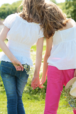 girls holding hands: Two girls holding hands Stock Photo