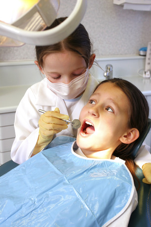 A girl disguising as a dentist treating a young patient photo
