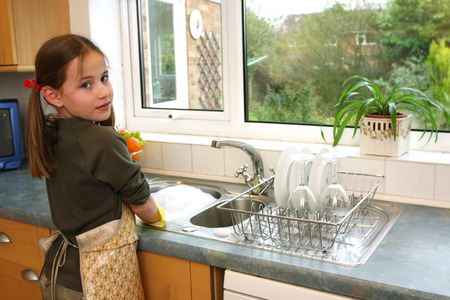 A girl in apron washing dishes in the kitchen photo