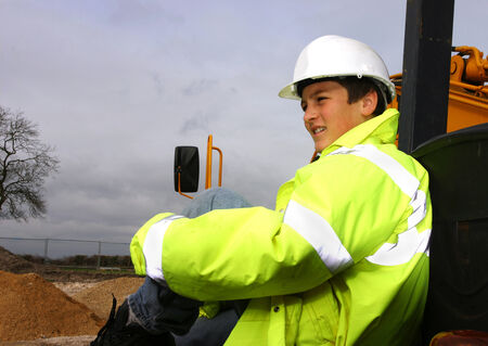 leaning on the truck: A boy in protection suit leaning on a truck at a construction site Stock Photo