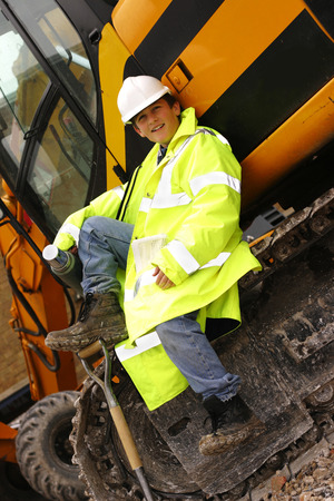 A boy sitting on an excavator holding a thermos flask photo