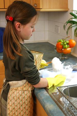 wash dishes: Vista lateral de una niña en lavar los platos delantal Foto de archivo