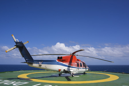 rescue helicopter: Helicopter shut down engine on oil rig helipad with blue sky Stock Photo