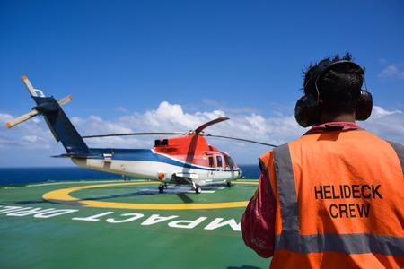 Hubschrauberlandedeck Crew kümmern Hubschrauber Motorabschaltung auf Bohrinsel Hubschrauberlandeplatz mit blauem Himmel