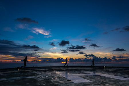 offshore jack up rig: Three men running on oil rig helipad in Gulf of Thailand in sunset time with helipad light on