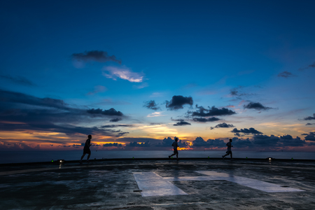 helipad: Three men running on oil rig helipad in Gulf of Thailand in sunset time with helipad light on
