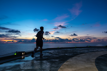 morning blue hour: Man running on oil rig helipad in Gulf of Thailand in sunset time with helipad light on