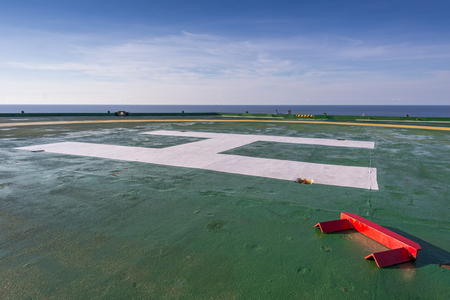 chock: Red chock on the green oil rig helipad in Gulf of Thailand with blue sky