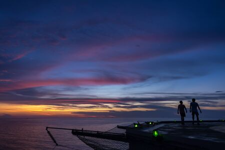 helipad: Two men walking on oil rig helipad when sunset time and green edge light on Stock Photo