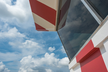 control tower: Air traffic control tower with red and white paint and scatterd cloud Stock Photo