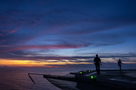 offshore jack up rig: Two men walking on oil rig helipad when sunset time and green edge light on Stock Photo