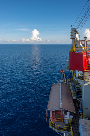 starboard: Emergency boat at starboard side of jack up oil rig in the blue ocean with blue sky