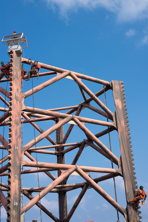 fall arrest: Men working at top of oil rig leg for painting