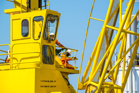 'rig out': Oil rig workers working at yellow crane electic crane with crane boom up with blue sky