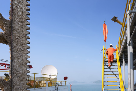 Worker walking up stairs to oil rigs helipad to check over before moving rig to other location with mountain Stock Photo