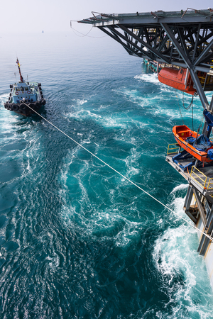 ship bow: Boat towing jack up oil and gas rig from the shipyard to the open sea