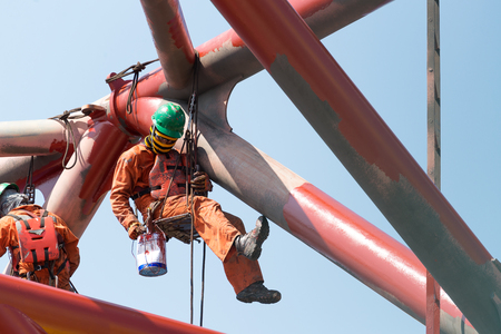 Workers working at height to paint the jack up oil and gas rig with full personnel protective equipment Standard-Bild