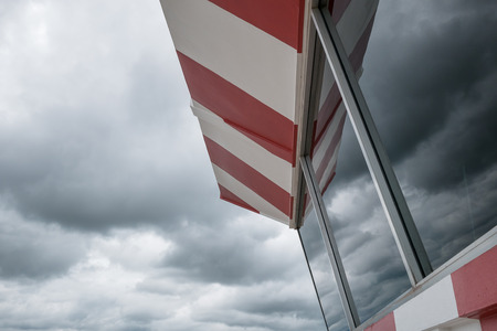 aerodrome: Aerodrome control tower painted chekered red and white with cloudy sky