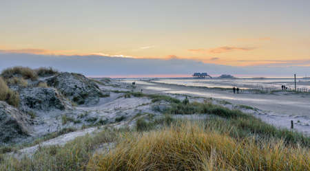 Dune landscape view of a beach and stilt houses, St Peter-Ording, North Friesland, Germany, Europe.