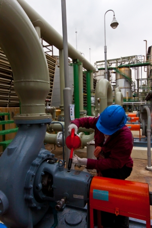 man at work filling oil pump in power factory