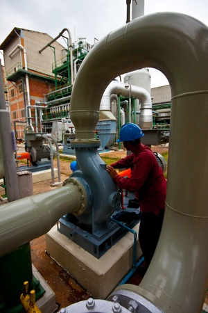 man at work filling oil pump of a power factory