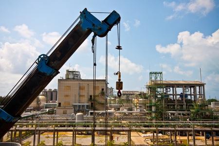 transporte terrestre: de la grúa de pie en un sitio de construcción en las plantas petroquímicas de la construcción Editorial