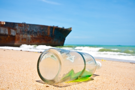 the bottles and old boat in the beach. Stock Photo - 14076204