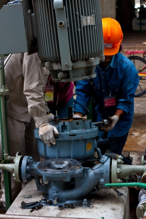 petrochemie industrie: werknemers repareren sundyne pomp in petrochemische fabriek
