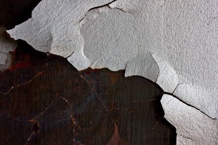 rusty background A rusty old metal plate with cracked white gloss paint photo
