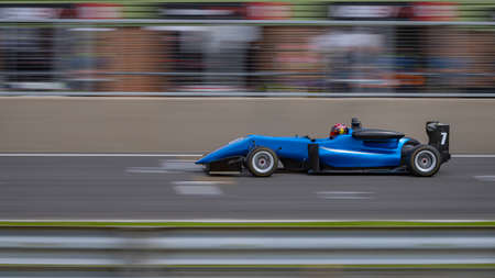 A panning shot of a blue racing car as it circuits a track.