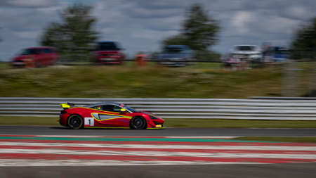 A panning shot of a red and yellow racing car as it circuits a track.