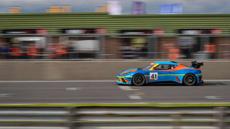 A panning shot of a blue and orange racing car as it circuits a track.