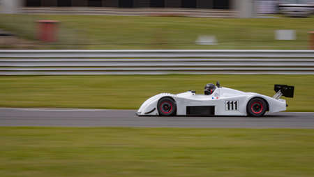 A panning shot of a white racing car as it circuits a track.