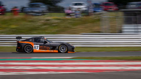 A panning shot of a black and orange racing car as it circuits a track.