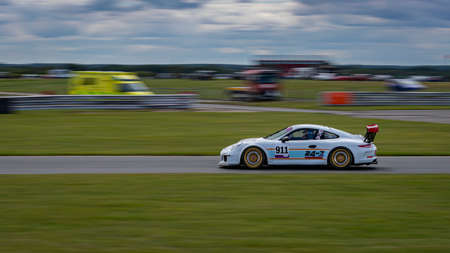 A panning shot of a white racing car as it circuits a track. Standard-Bild