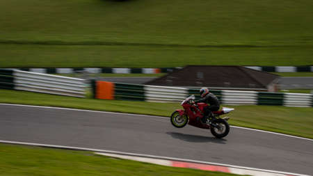 A panning shot of a racing bike on one wheel on a track.