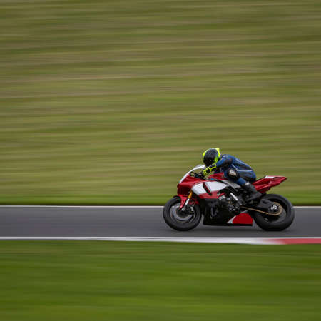 A panning shot of a racing bike cornering on a track.