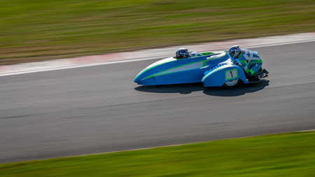A panning shot of a racing sidecar as it corners on a track. Stock Photo