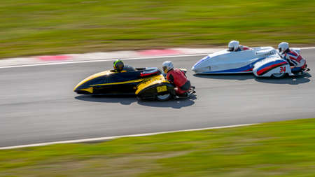 A panning shot of two racing sidecars as they corner on a track. Фото со стока