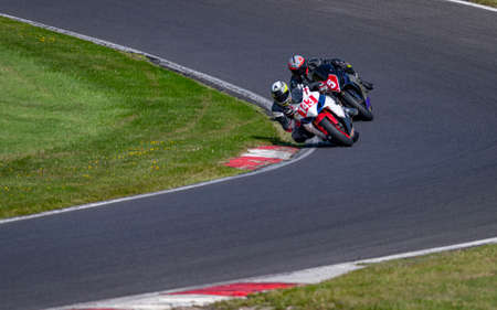 A shot of two racing bikes cornering on a track.
