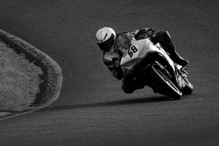 A monochrome shot of a racing motorbike as it circuits a track.