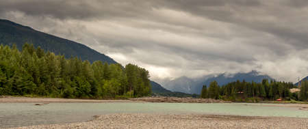 Flat, glacial blue back channel on the Skeena River at Gravel Yard Point, Terrace, British Columbia, Canada