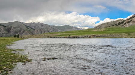 A fast river in Mongolia, with mountains, blue sky and grassland in the background,