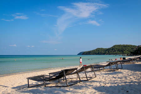 A fish shaped cloud over Sao Beach, with tourist sun loungers in the foreground, Phu Quoc, Vietnam
